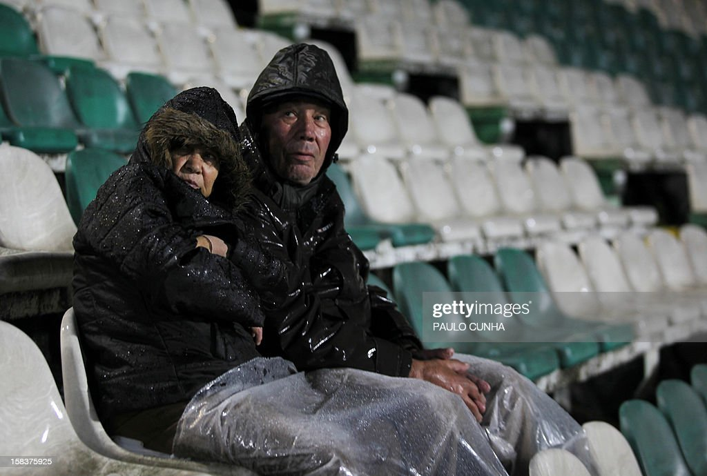 Football supporters shelter from the rain as they sit in the grandstands before the Portuguese league football match VSC Setubal vs FC Porto on December 14, 2012 at Bonfim stadium in Lisbon. The match was postponed due to bad weather conditions.