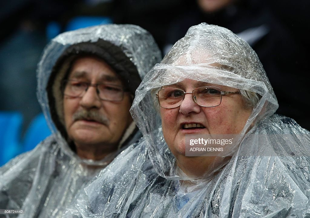 Football supporters wear waterproofs before the English Premier League football match between Manchester City and Leicester City at the Etihad Stadium in Manchester, north west England, on February 6, 2016. / AFP / ADRIAN DENNIS / RESTRICTED TO EDITORIAL USE. No use with unauthorized audio, video, data, fixture lists, club/league logos or 'live' services. Online in-match use limited to 75 images, no video emulation. No use in betting, games or single club/league/player publications. /