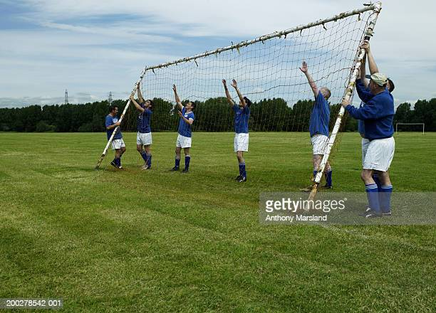 Football team erecting goal on pitch
