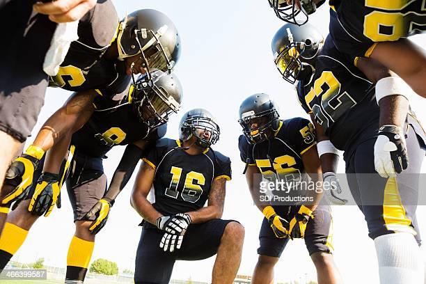 Équipe de Football huddled pendant le temps tout en jouant au jeu
