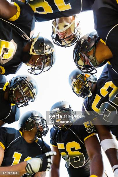 Football team huddling together during game time out