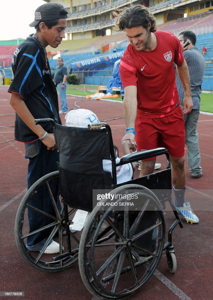 US football team player Sacha Kijestan (R) shakes hands with a child on a wheelchair during a training session at the Olimpico Metropolitano stadium, in San Pedro Sula, 240 km north of Tegucigalpa, on February 5, 2013. The US will face Honduras on Wednesday on a WC2014 Concacaf qualifier football match. AFP PHOTO/Orlando SIERRA
