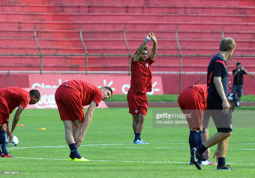 US football team players stretch during a training session at the Olimpico Metropolitano stadium, in San Pedro Sula, 240 km north of Tegucigalpa, on February 5, 2013. The US will face Honduras on Wednesday on a WC2014 Concacaf qualifier football match. AFP PHOTO/Orlando SIERRA