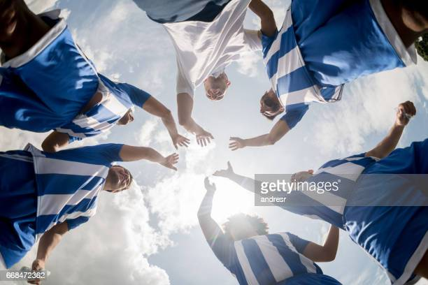 Football team with hands together celebrating victory