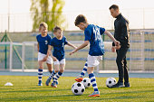 Football Training Practice Exercises for Youth Soccer Players. Boys on Training with Soccer Balls on Pitch