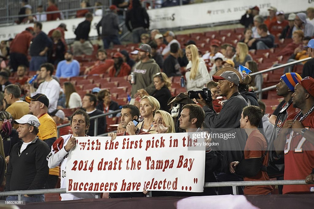 View of Tampa Bay Buccaneers fan holding sign reading WITH THE FIRST PICK IN THE 2014 DRAFT, THE TAMPA BAY BUCCANEERS HAVE SELECTED... in stands during game vs Carolina Panthers at Raymond James Stadium. Gary Bogdon TK1 )