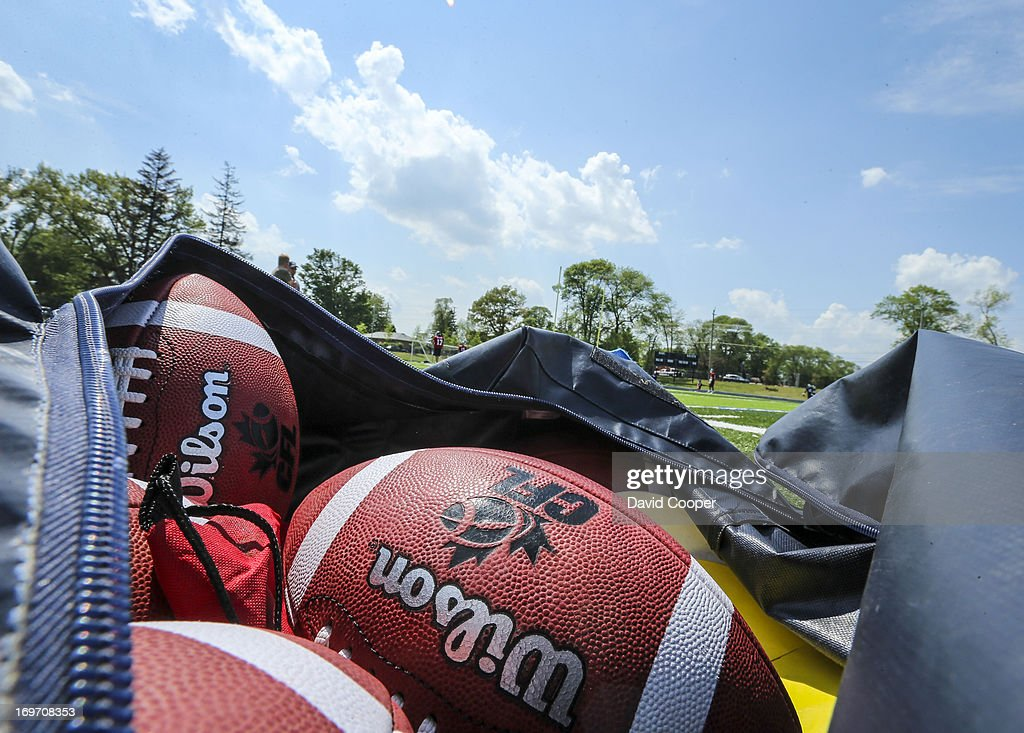 Football wait on the sidelines as the Argos take to the field during the 2nd day of Argos rookie camp at St. Thomas Aquinas High School field.