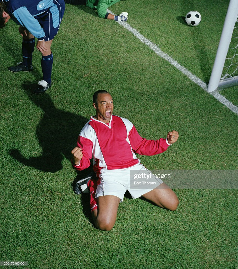 Footballer celebrating on pitch, elevated view : Stock Photo