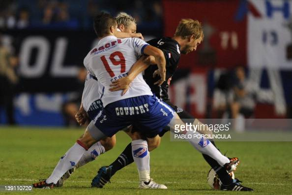 Footballer Cristian Menendez of Paraguayan team Libertad is marked by Andres Scotti and Israel Damonte of Uruguay's Nacional during their...
