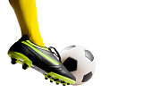 Isolated Close up shot of footballer feet kicking soccer ball over white background