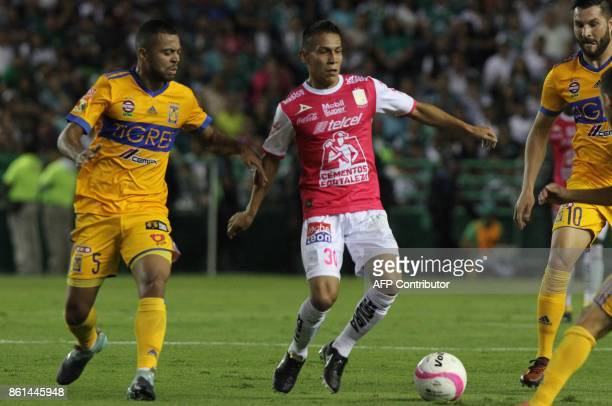 Footballer Jose Rodriguez of Leon is marked by Tigres' Brazilian Rafael de Sousa and French Andre Gignac during their Mexican Apertura tournament...