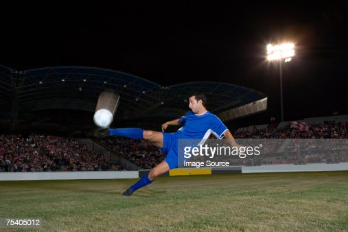 Footballer kicking ball : Stock Photo