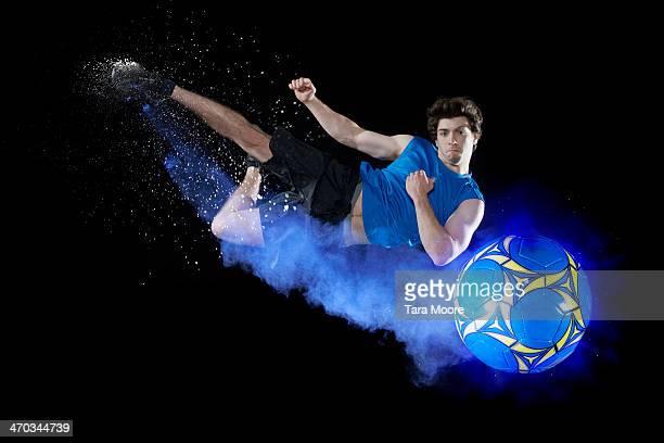 footballer kicking ball with blue smoke