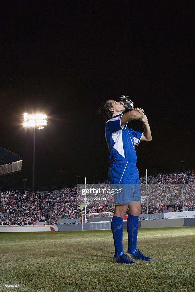 Footballer kissing trophy : Stock Photo