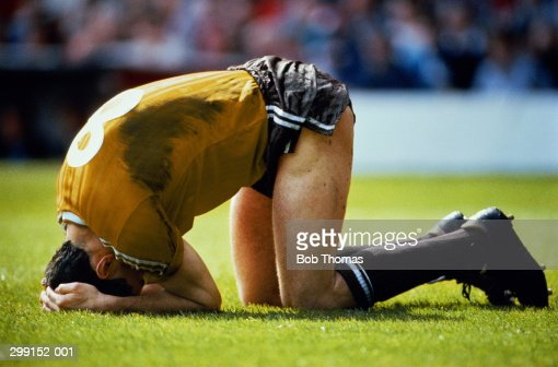 Footballer lying on ground with head in hands (Colour Enhanced)