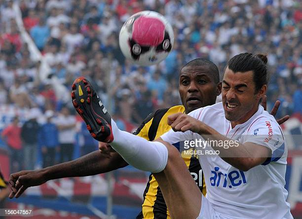 Footballer Marcelo Zalayeta of Peñarol and Alejandro Lembo of Nacional vie for the ball during their derby match of the Uruguayan tournament at the...