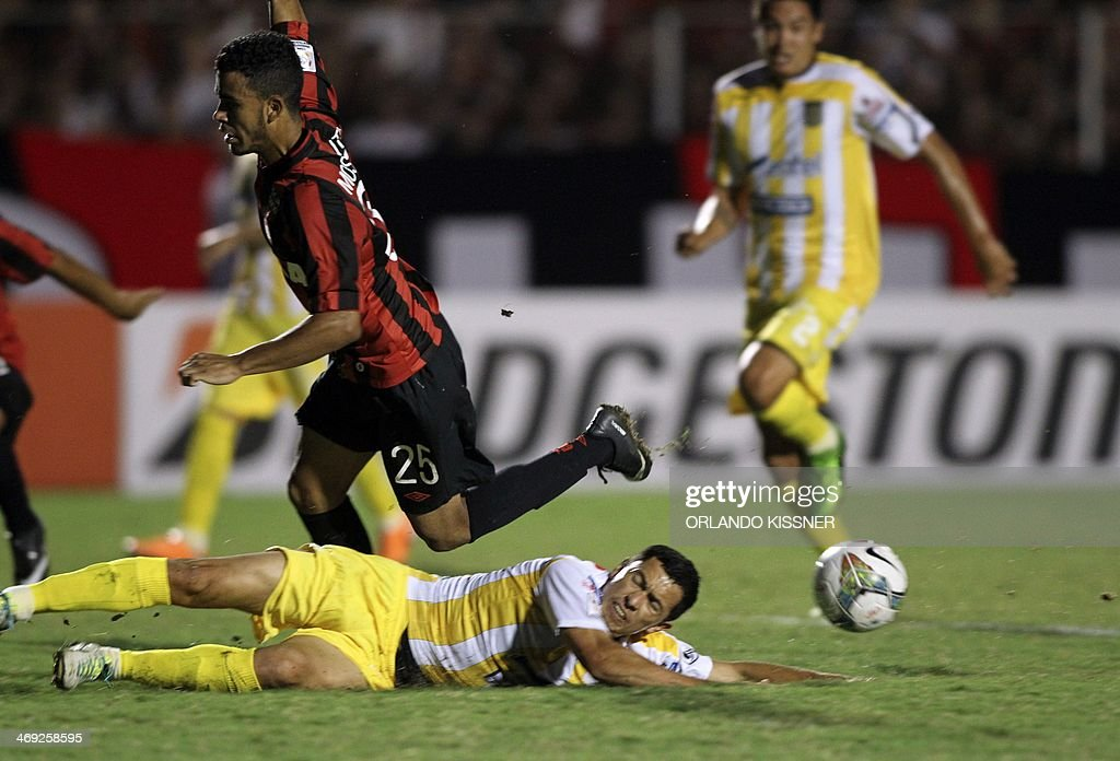 Footballer Mosquito (top) of Brazil's Atletico Paranaense, falls over a player of Bolivia's The Strongest during a Libertadores Cup football match held at the Vila Capanema stadium in Curitiba on February 13, 2014.