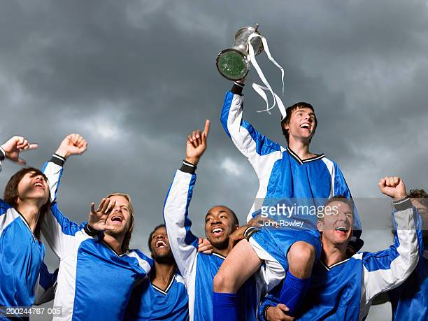 Footballer players celebrating, one raised by others, waving trophy