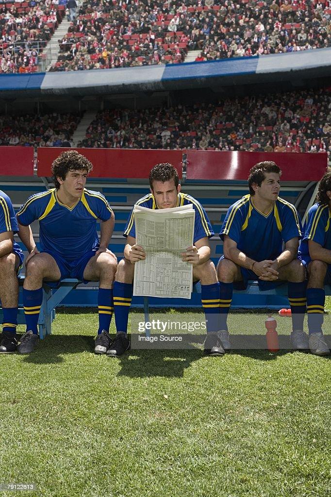 Footballer reading a newspaper