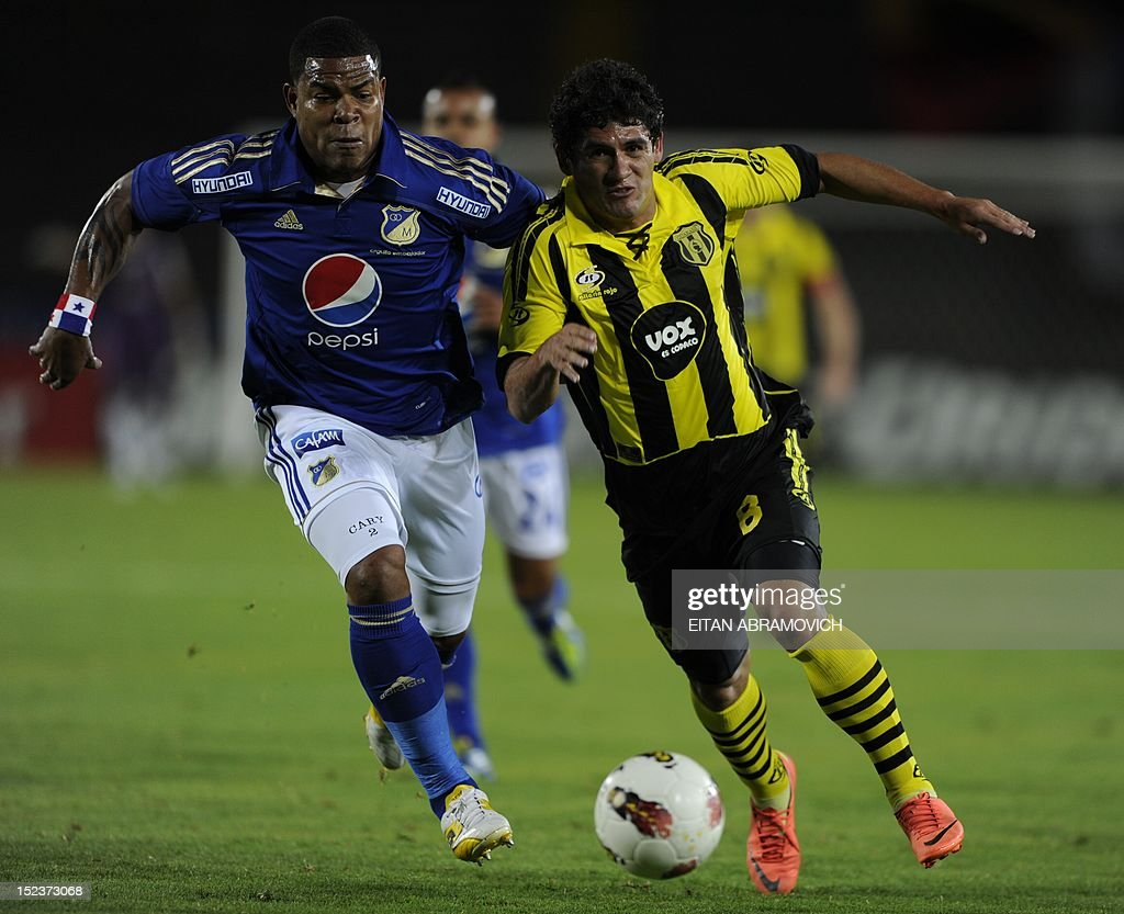 Footballer Roman Torres (L) of Colombian team Millonarios vies for the ball with Antonio Caceres of Paraguay's Guarani during their Copa Sudamericana football match in Bogota on September 19, 2012. AFP PHOTO/Eitan Abramovich