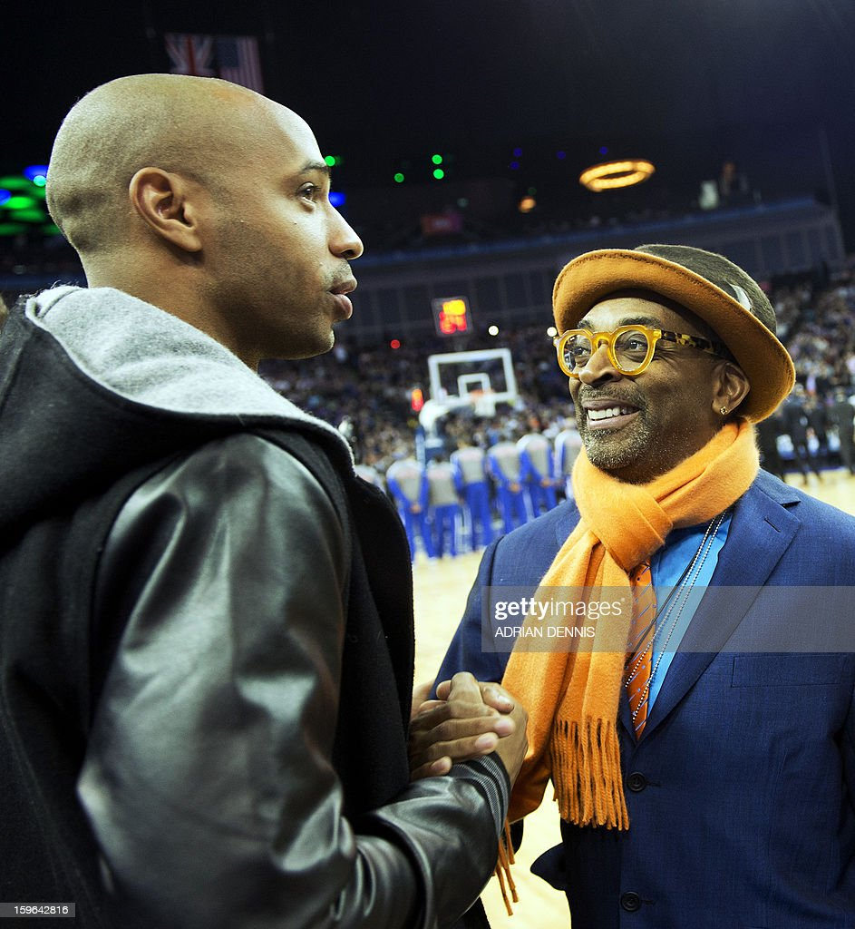 Footballer Thierry Henry (L) and film director Spike Lee (R) greet each other ahead of the NBA basketball game between The New York Knicks and The Detroit Pistons at the O2 Arena in London on January 17, 2013.