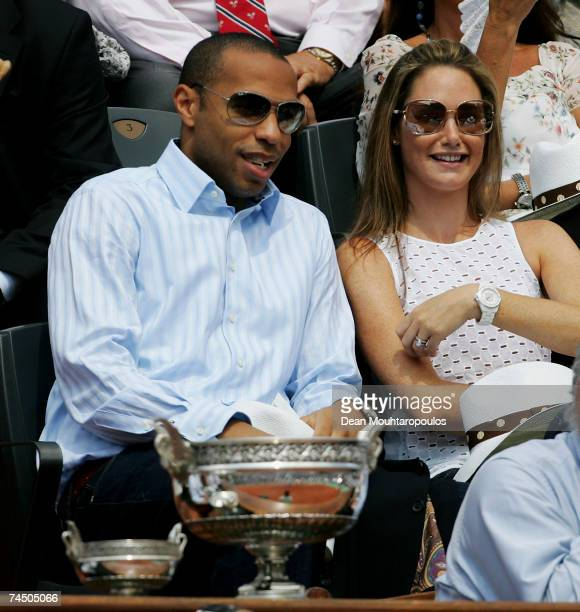Footballer Thierry Henry and his wife Nicole Merry sit in front of the Philippe Chatrier Trophy as they watch Roger Federer of Switzerland and Rafael...