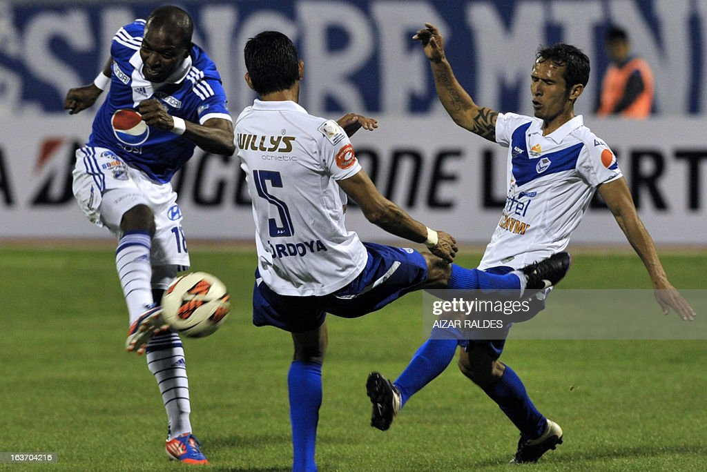 Footballer Wason Renteria (L) of Colombia's team Millonarios, is marked by Carlos Tordoya (C) and Roly Sejas of Bolivia's San Jose during their Libertadores Cupl match at Jesus Bermudez stadium in Oruro, Bolivia, on March 14, 2013. AFP PHOTO/Aizar Raldes