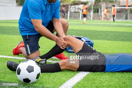 Footballer wearing a blue shirt, black pants injured in the lawn during the race. : Foto de stock