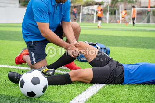 Footballer wearing a blue shirt, black pants injured in the lawn during the race. : Stock Photo
