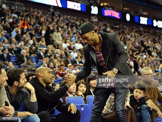Footballers Cesc Fabregas and Thierry Henry greet Didier Drogba during the 2015 NBA global game between Milwaukee Bucks and New York Knicks at the O2...