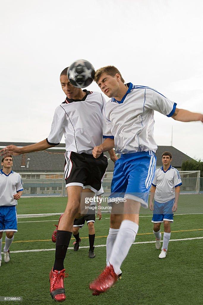 Footballers heading ball : Stock Photo