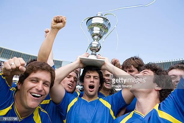 Futbolistas que agarra un trofeo