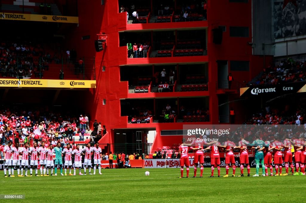Footballers of Necaxa (L) and Toluca pay a minute of silence for the victims of the terrorist attack in Barcelona before their Mexican Apertura football tournament match at the Nemesio Diez stadium in Toluca, Mexico, on August 20, 2017. /