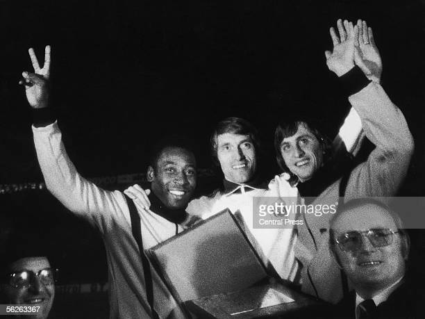 Footballers Pele Paul van Himst and Johann Cruyff wave to the crowd after van Himst farewell match between Anderlecht and a World XI 26th March 1975...