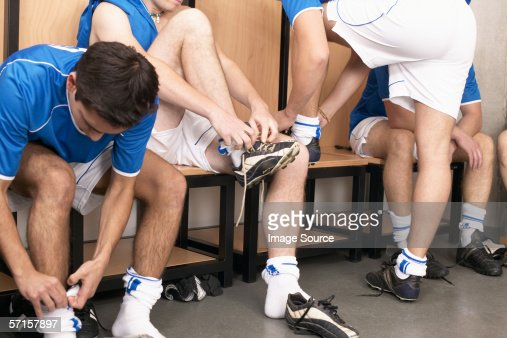 Footballers putting on boots : Stock Photo