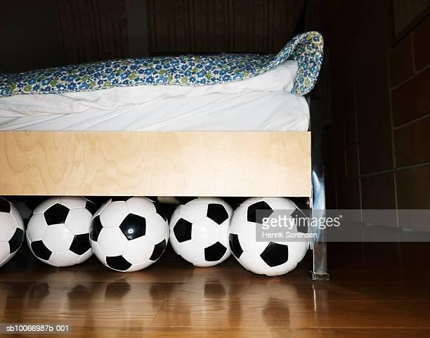 Footballs under bed in bedroom