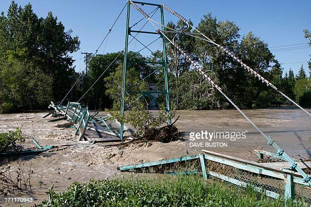 A footbridge is torn apart by the flooding at Elbow River in CalgaryAlberta Canada June 22 2013 AFP PHOTO/DAVE BUSTON