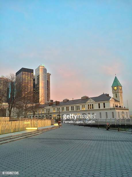 Footpath Leading Towards Illuminated Buildings At Battery Park Against Sky