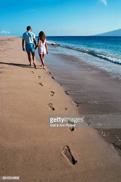 Footprints and Couple Walking on Beach
