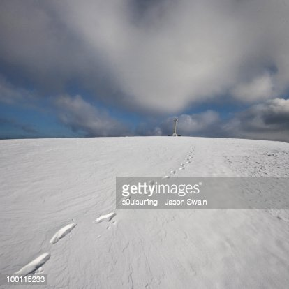 Footprints in snow leading to cross : Stock-Foto