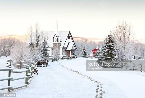 Impronte nella neve per un incantevole paese Chiesa in inverno.