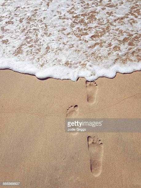 Footprints in the sand leading to the ocean