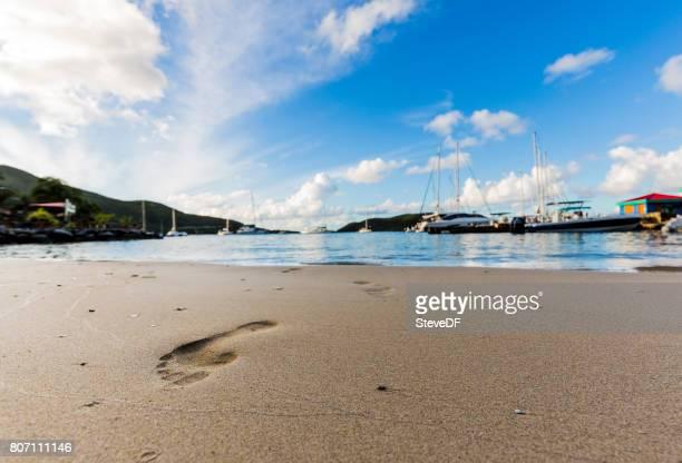 Footprints lead across the sand of a beautiful Caribbean beach