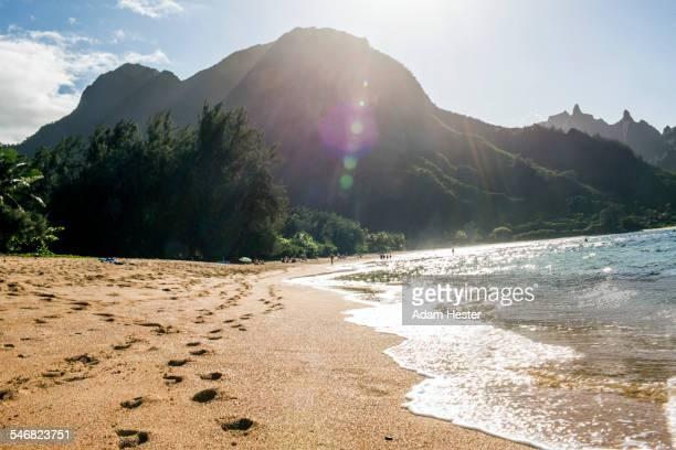 Footprints on sand near waves on tropical beach