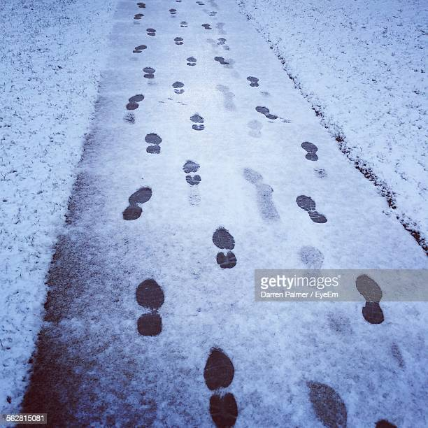 Footprints On Snow Covered Pathway