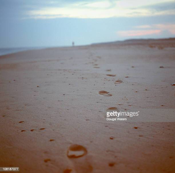 Footsteps on beach leading into distance.