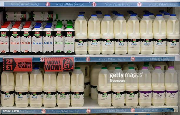 A '2 For £1' label sits on a shelf between bottles and cartons of fresh milk produced by Muller Wiseman Dairies displayed for sale in a chiller...