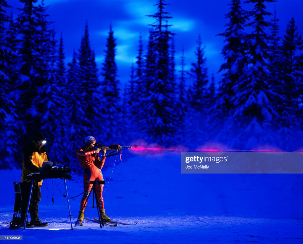 For each shot taken by ski-shod Carolyn Treacy of the U.S. junior national biathlon team, a laser tracks her aim, a sensor measures trigger pressure, and a camera records the recoil on December 01, 1999 during training near Silver Star Mountain, British Columbia. Behind her, engineer Tim Conrad studies results on a computer.