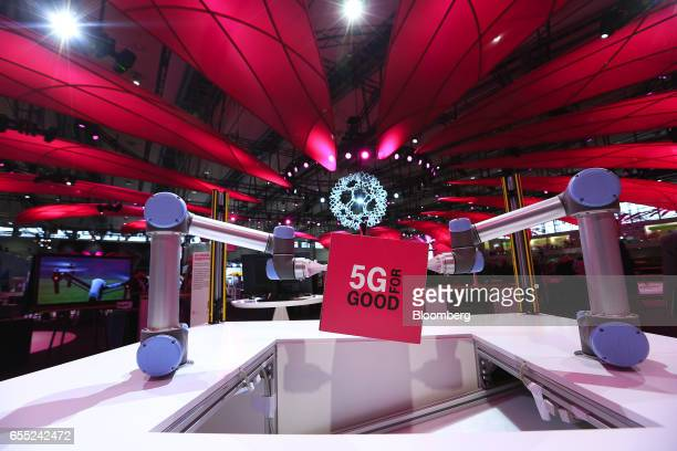 A '5G for Good' advertisement hangs from robotic arms in the Deutsche Telekom AG pavilion at the CeBIT 2017 tech fair in Hannover Germany on Sunday...