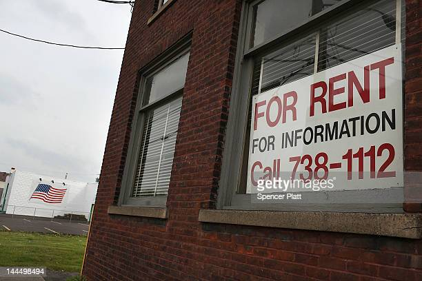 A 'for rent' sign hangs in a window of an empty factory on May 14 2012 in Utica New York Like many upstate New York communities Utica is struggling...